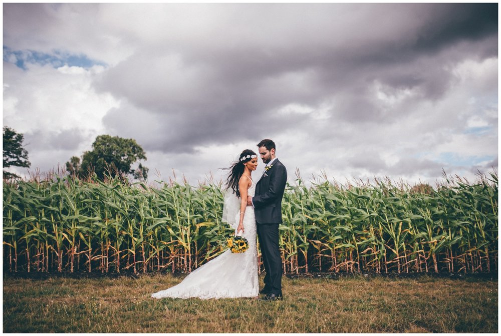 Bride and groom have their wedding photographs taken in a corn field at Sandhole Oak Barn in Cheshire.