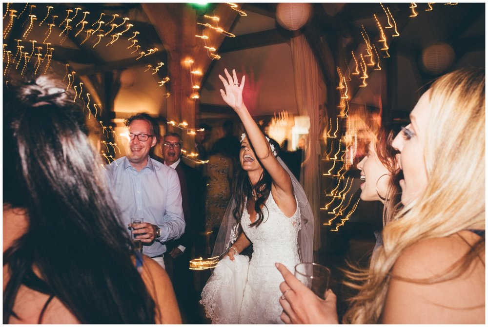 Beautiful bride dances at her wedding at Sandhole Oak Barn in summer wedding in Cheshire.