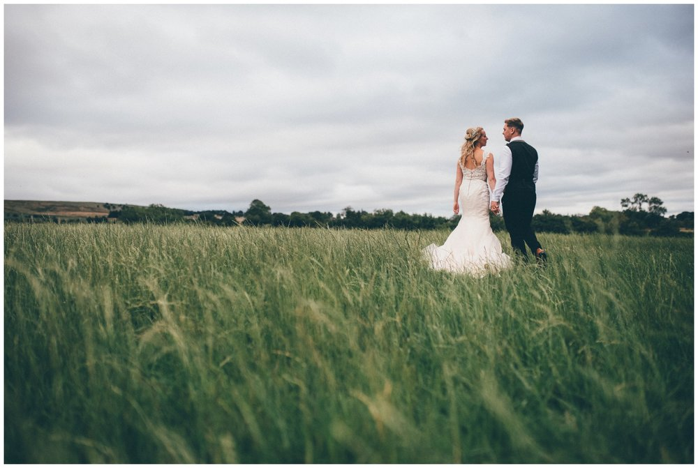 Staffordshire bride and groom walk through a field together on their wedding day near their tipi.