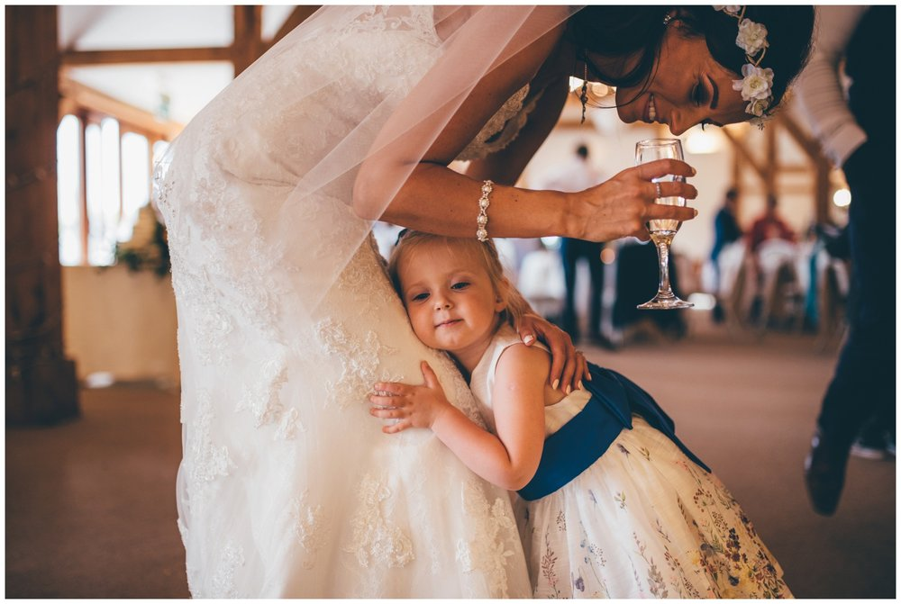 Cute little flower girl cuddles the bride at Sandhole Oak Barn in Cheshire,