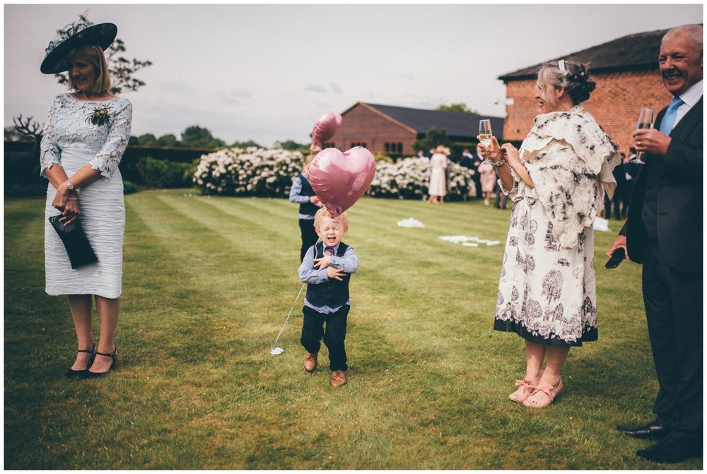 Adorable wedding guest at new wedding venue in Cheshire, Merrydale Manor  runs at an inflatable balloon.