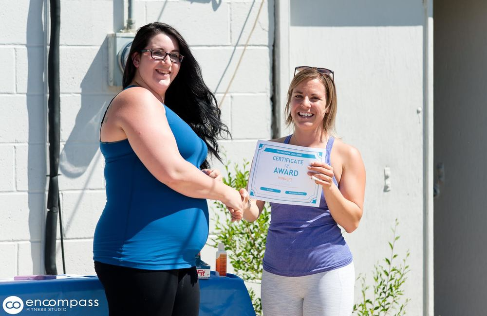 Kandyce Meili (left) the winner our of May TakeDown Challenge receiving her award of one month of personal training and a Shaklee care package from Encompass Fitness Owner Brady Johnson (right).