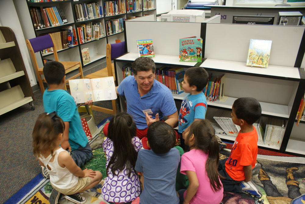 Michael Roch reads to inquisitive students in the elementary library.