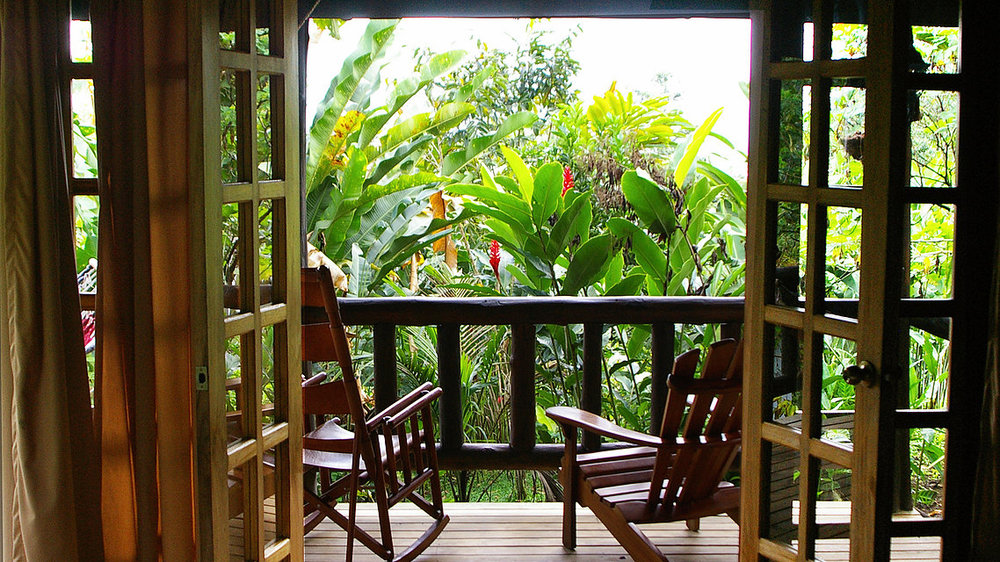 Relax and unwind in your bungalow on a private deck overlooking tropical gardents