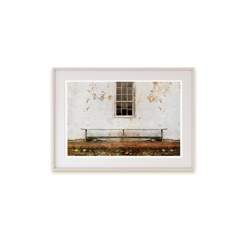 A color print of a wooden bench print set against a peeling old building