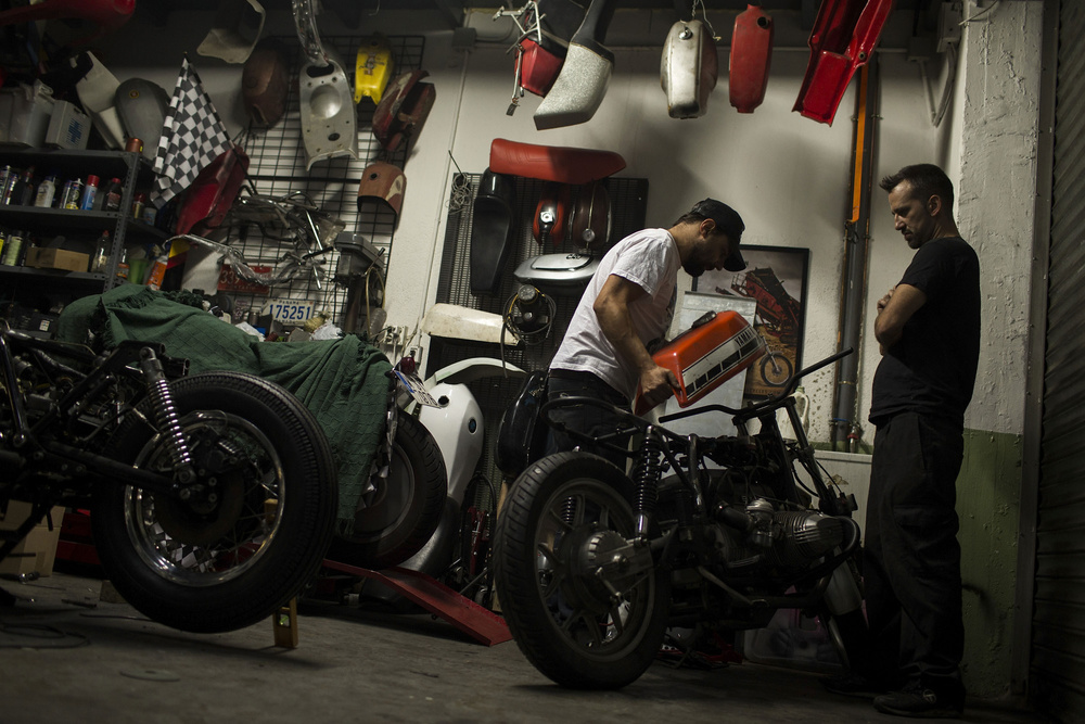 Fede and his fellow Alvaro (Iron specialist) try to fit together a  Yamaha RD 400 motorbike ´s  tank  with The Altamirano´s chasis (a B MW R65 LS ) in  Café Racer Obsession (CRO) garage  on Ocober 13, 2014 in Madrid Spain. Cast sculptors, a community trader and a musician have something in common: they have made the passion of customizing motorbikes their own business. Valtoron Sculptured Motorcycles, Café Racer Obsession and El Solitario Motorcycles are the dreams-come-true of the Delgado Brothers, Federico Ruiz and David Borrás.