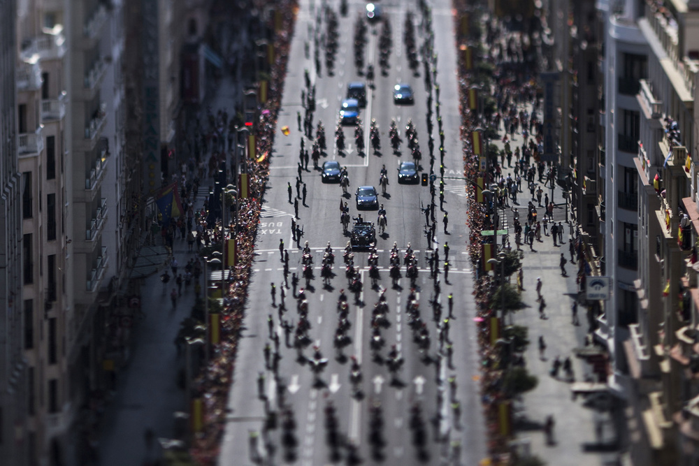 King Felipe VI  and Queen Letizia of Spain wave to the crowds during his  coronation 's  procession  down the  Gran Via  on June 19, 2014 in  Madrid , Spain (This image was created with a variable plane focus lens known as  tilt & shift ).