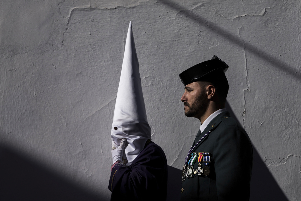 "A  Civil Guard  walks behind a  penitent  during the  Holy Week   procession  of""Nuestro Padre Jesus  Nazareno "" Brotherhood on April 2, 2015 in  Arriate , Spain. In many towns of Spain four Civil Guards use to ""escort""  Nazarene   thrones  during their Holy Week processions. In Spain many of the State Security Forces have patron saints or worship Catholic figures such as Virgins or Christs."