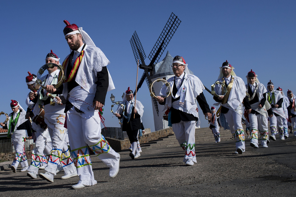 "Danzantes walk ahead a  mill  durin the forth day of "" Pecados y Danzantes "" processions on June 7, 2015, in  Camuñas , Castilla la Mancha, Spain. In order to celebrate the the  Catholic  feast of  Corpus Christi , people divided in two groups (Pecados and Danzantes) perform a "" dance "" as they walk in procession across Camuñas town. ""Pecados"" symbolize the Evil and are dressed up with terrorific masks and black ornamented dresses, while ""Danzantes"" symbolize the  Virtue  and are dressed up with white attires and  big-nosed mask s. The beginnings of this tradition come from the  16th Century  and could be considered as a kind of "" Auto Sacramental ""."