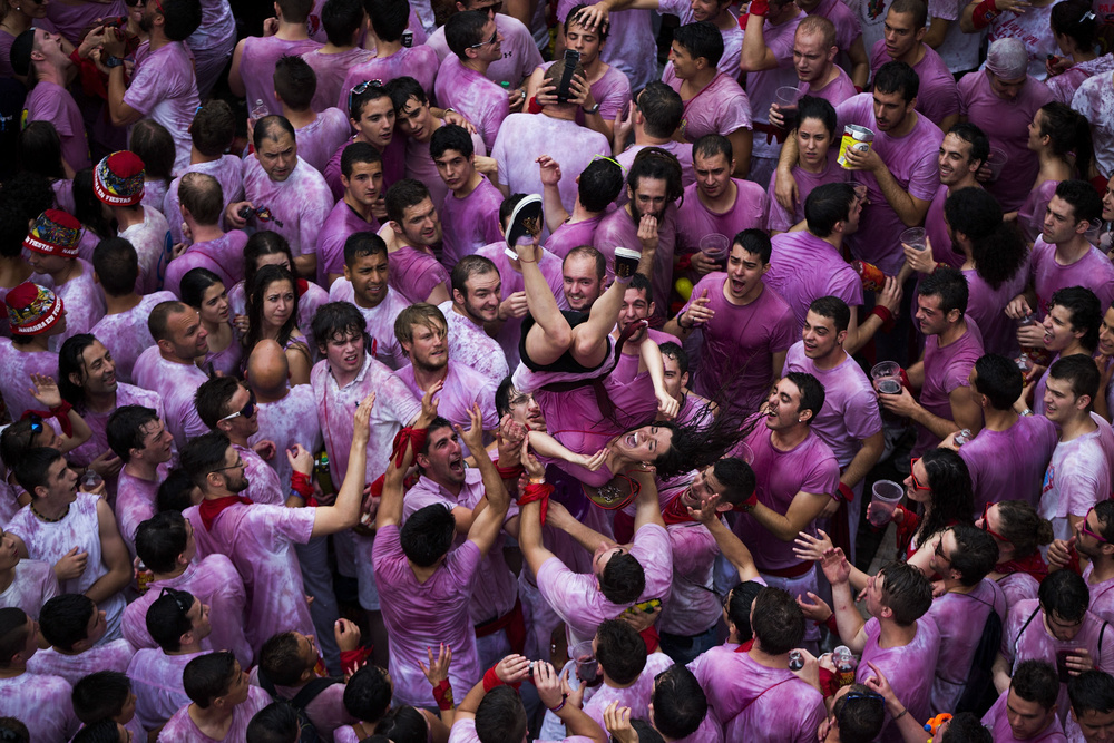 "A  woman  is cheered by  revelers  minutes before the launch ofthe "" Txupinazo "" rocket to celebrate the official opening of the 2014  San Fermin Festivities  at the City Council Square on June 6, 2014 in  Pamplona , Spain. Revelers arrived from around the world kick off the festival with a messy party, one day before the first of eight days of the running of the bulls glorified by Ernest  Hemingway 's 1926 novel ""The Sun Also Rises."""