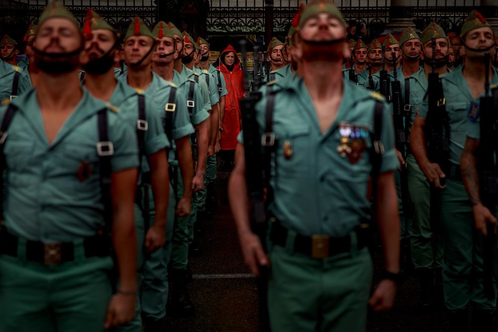 A woman looks at  Spanish Legionnaires  as they from prior to start their parade during the  Spain National Day  on  October 12 , 2016 in madrid Spain. The 12th of October Spain commemorates the arrival of Christopher Columbus to America. Each year a big militar march-past which is hired by the Spanish king is held in Madrid.