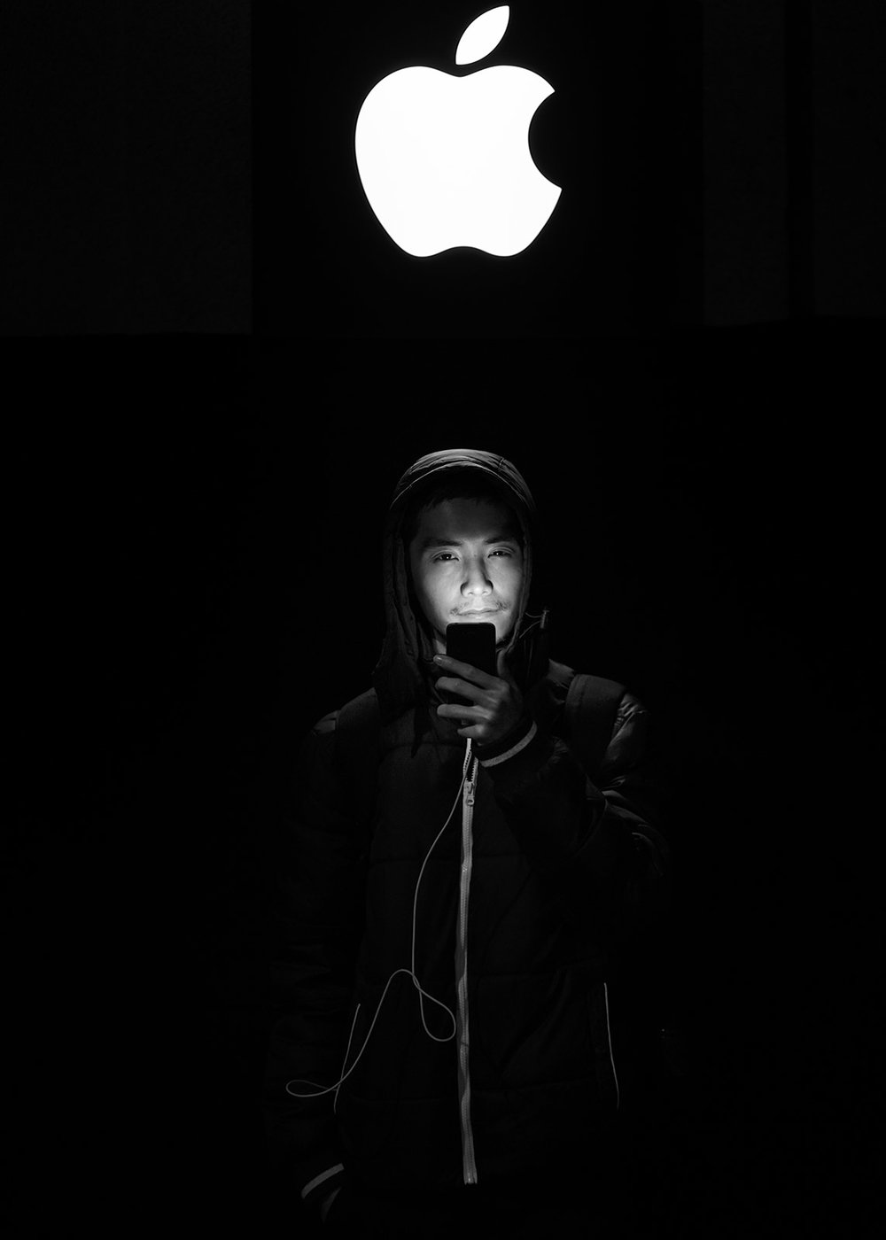 Son Nguyen Thai from  Vietnam  poses for a picture as he illuminates himself with his mobile phone at  Puerta del Sol Apple Store  facade the dawn before the company launches their  Iphone 7  and 7 Plus on September 16, 2016 in Madrid, Spain. Cooking student Son Nguyen Thai, 28, waited for 10 hours at Puerta del Sol Apple Store outdoors in order to purchase his second Iphone model: an Iphone 7.