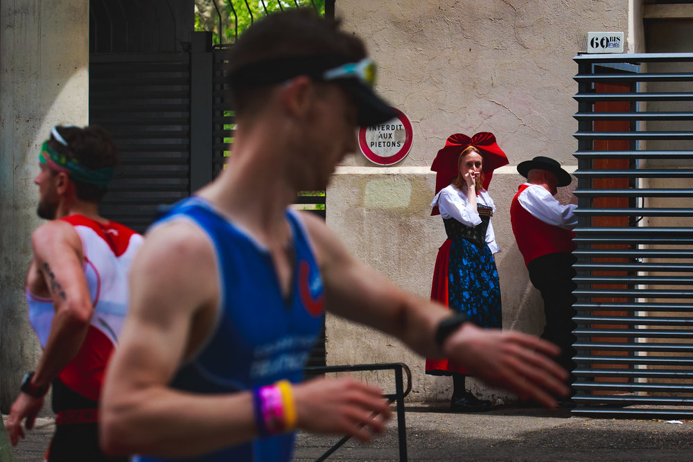A woman dressed up with traditional costumes looks to athletes as they compete during the running course of the Ironman 70.3 - Pays d'Aix on May 14, 2017 in Aix-en-Provence, France.