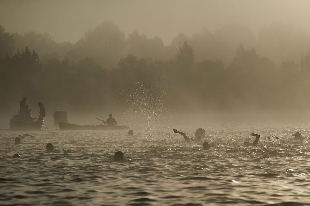 Athletes warm up prior to start he Ironman 70.3 - Pays d'Aix swimming course on May 14, 2017 as the fog clears up at Lake Peyrolles, France.