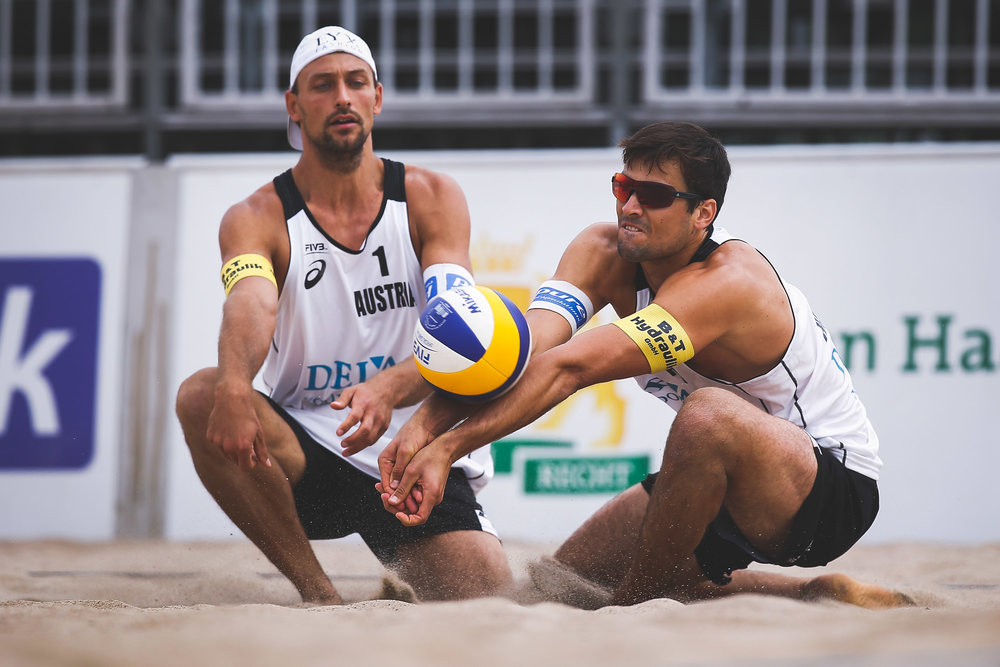 Christoph Dressler (R) from Austria bumps the ball ahead his partner Thomas Kunert (L) during their match against The Netherlands during the FIVB Beach Volleyball World Tour at the Sportcampus Zuiderpark on June 16, 2017 in The Hague, Netherlands.