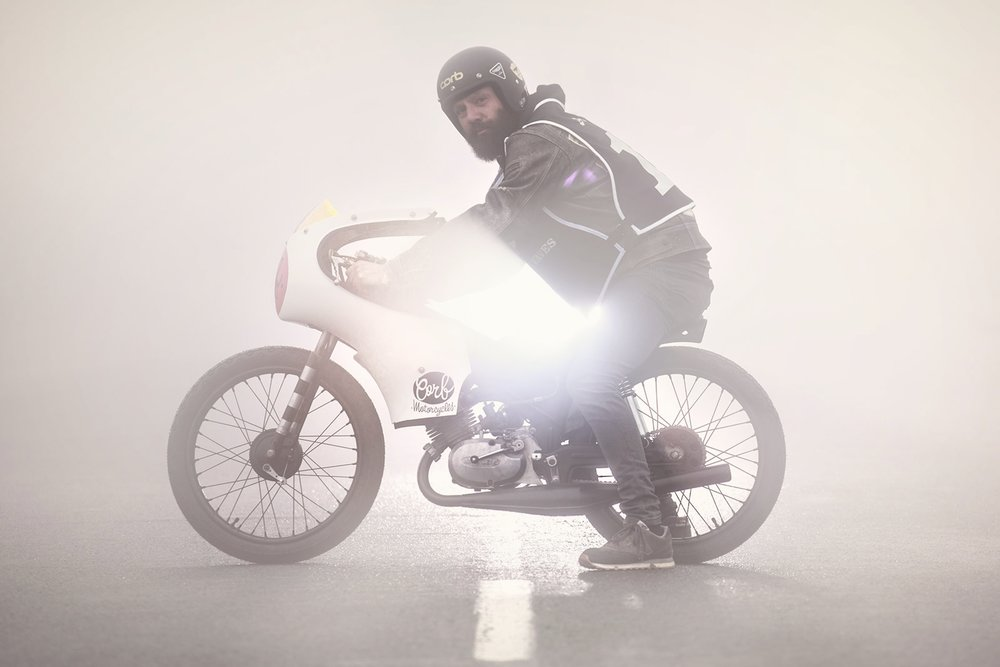 "Motorcycle  craftsman Xanti Garcia ( Corb Motorcycles ) poses for a picture with his ""La Pena Negra"" bike during the  Pun's Peak  race at  Jaizkibel  Mountain on June 10, 2016 in Guipuzcoa province, Spain. ""La Pena Negra"" is a customisation of a 50cc  Derbi Antorcha  bike made exclusively for La Copita/ Pun's Peak race. This race was held during the  Weels & Waves  festival and was the idea of customiser David Borras ( El Solitario MC ). The race was inspired in the former straight-line races hold on roads decades before. The only rule to join this 400 meters race was coming with a  50cc  bike customised for the event. 17 riders attended the 2016 edition but the race was canceled on the last minute due to a dense  fog ."