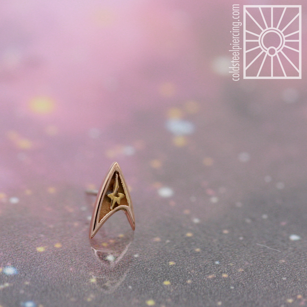"Get ready to set your phasers to ""fun"" with these solid gold ""Space Geezer"" ends from Body Vision Los Angeles! These Starfleet insignias are sure to add some galactic glam to your piercing, and broadcast your love for all things Star Trek as you boldly go where no person has gone before ✨🖖🏼✨"