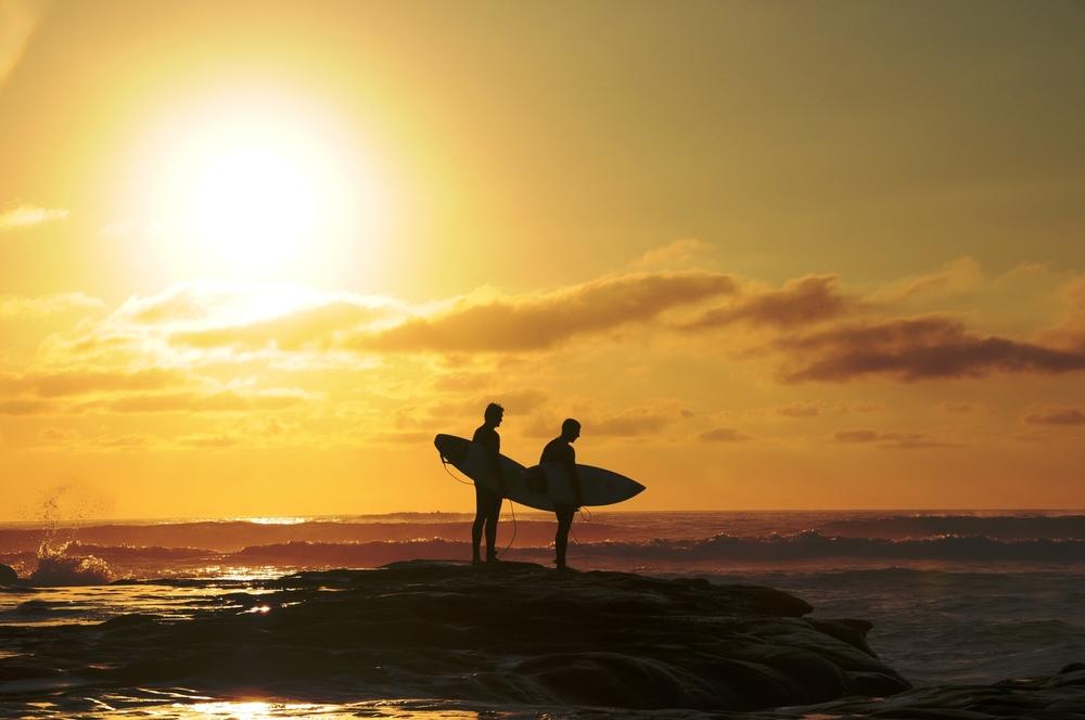 stock-photo-surfer-on-the-beach-at-sunset-211632091.jpg