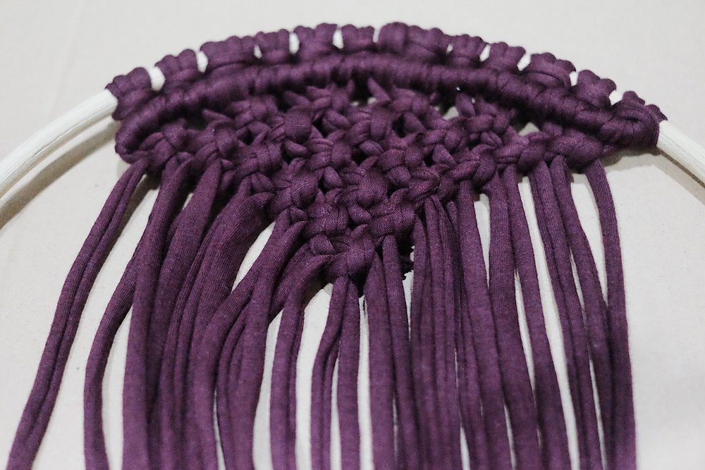 Noted:  *Using the strand of yarn that is furthest to the left (holding cord), place it horizontally over (from left to right) all other strands (working cords).   *Progressing from left to right, tie double half hitches with the remaining working cord to get a row of knots.