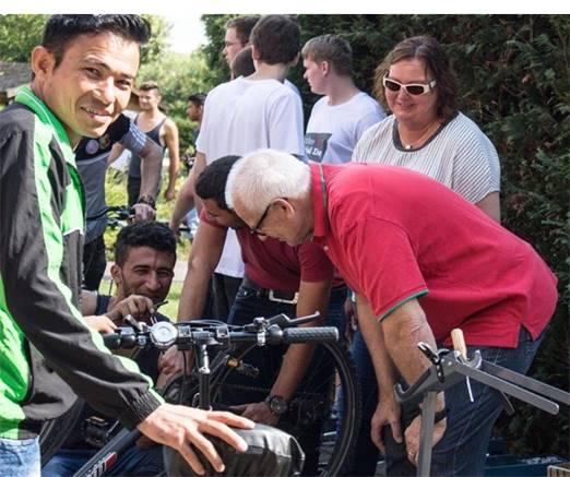 Geflüchtete und Ehrenamtliche werkeln gemeinsam in der Fahrradwerkstatt.
