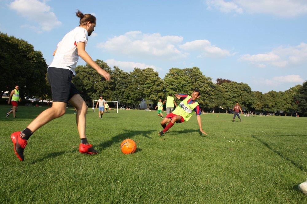 Gemeinsames Fußballspielen kann mit Trainingsmaterial wie Bällen unterstützt werden (i.d.R. keine Trikots!)