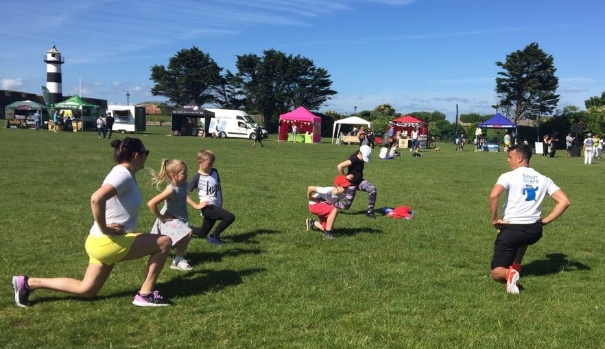 Demonstrating a lunge to the kids of Sweat outdoors.