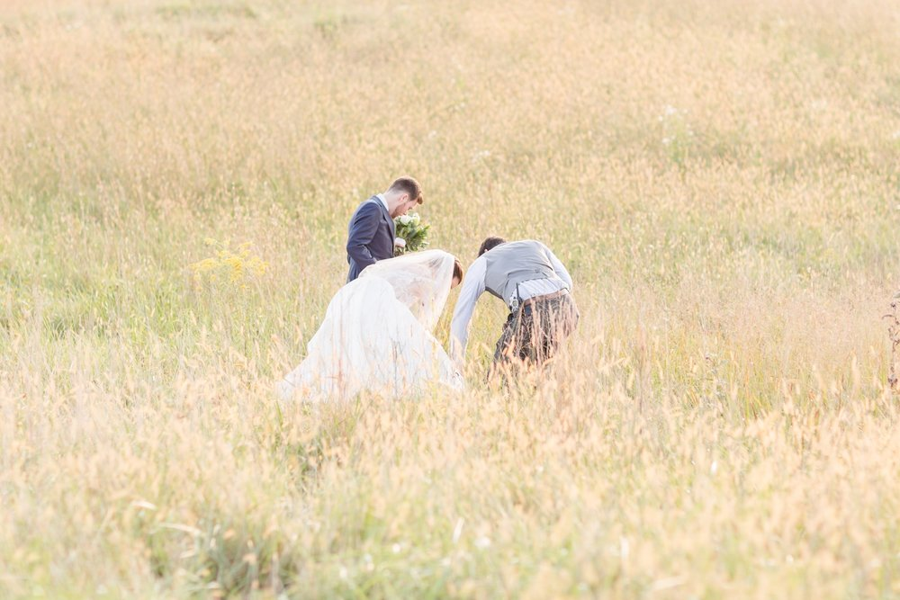 Kevin helping to make sure Kristen's dress didn't get caught in the field!