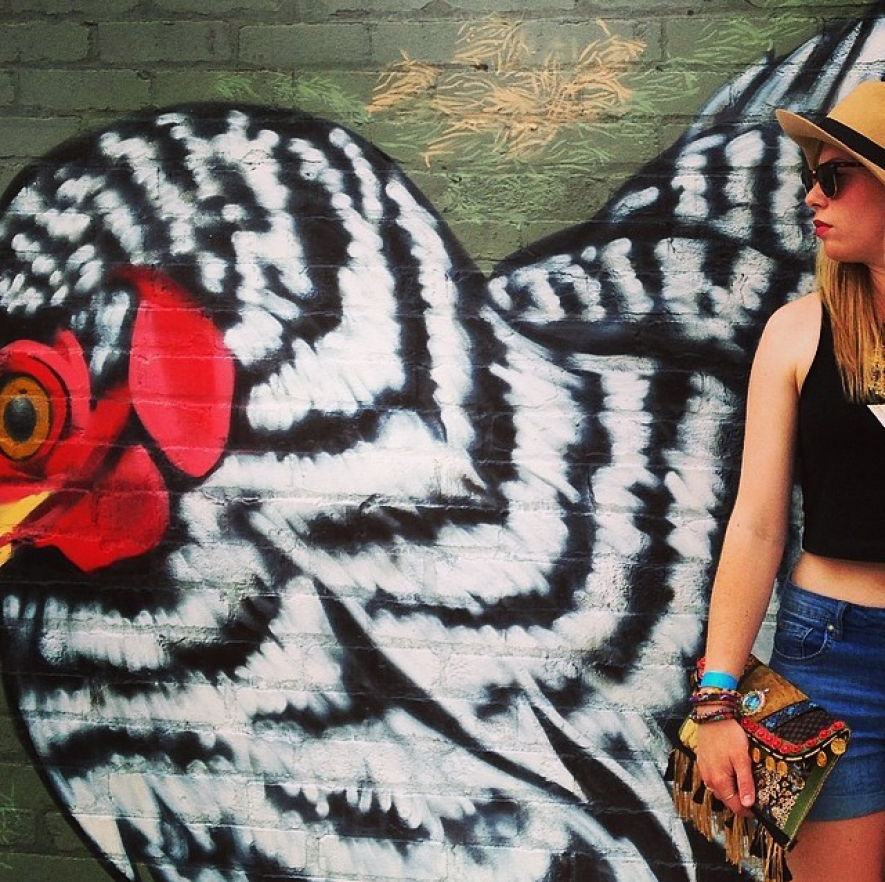Wearing a standard black crop top with high-rise denim and handmade clutch by a mural in Southside, Chattanooga.