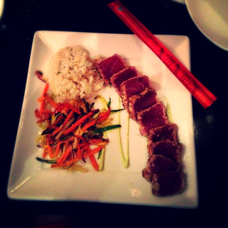Fresh tuna rolled in spices pan seared and served rare over wasabi aioli with sweet ginger rice and julienne vegetables.