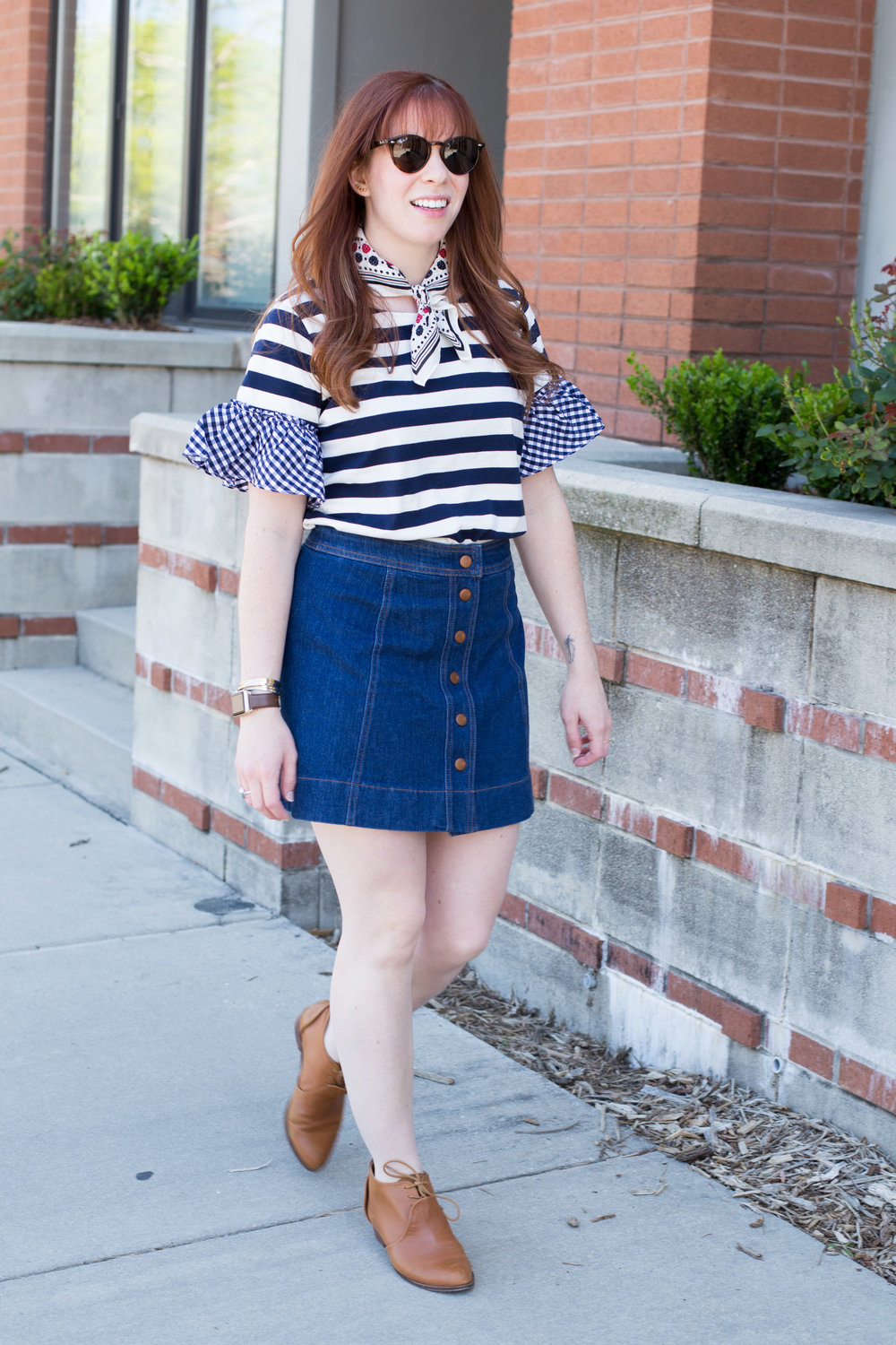 Adding a neck scarf to a simple blouse and flirty denim skirt is the perfect way to make a comfortable outfit unique. Find out more at www.thefashionablefoodieblog.com!
