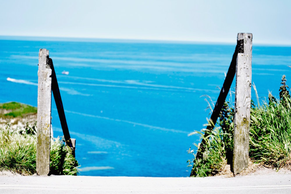 Wooden railing leading down to open, blue water