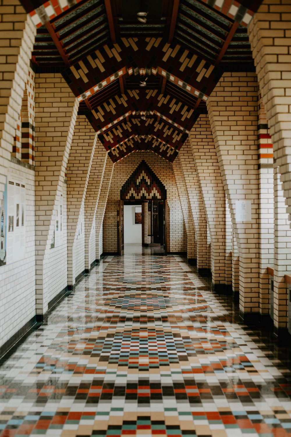 A tall hallway tiled in colors of tan, white, turquoise, red, and black in a geometric pattern, leading to a door at the end