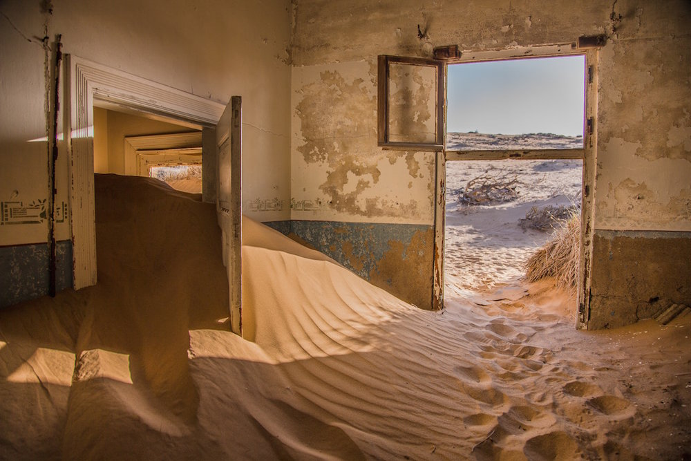 A rustic building in the desert, with sand flowing in through one door and another door leading out to horizon