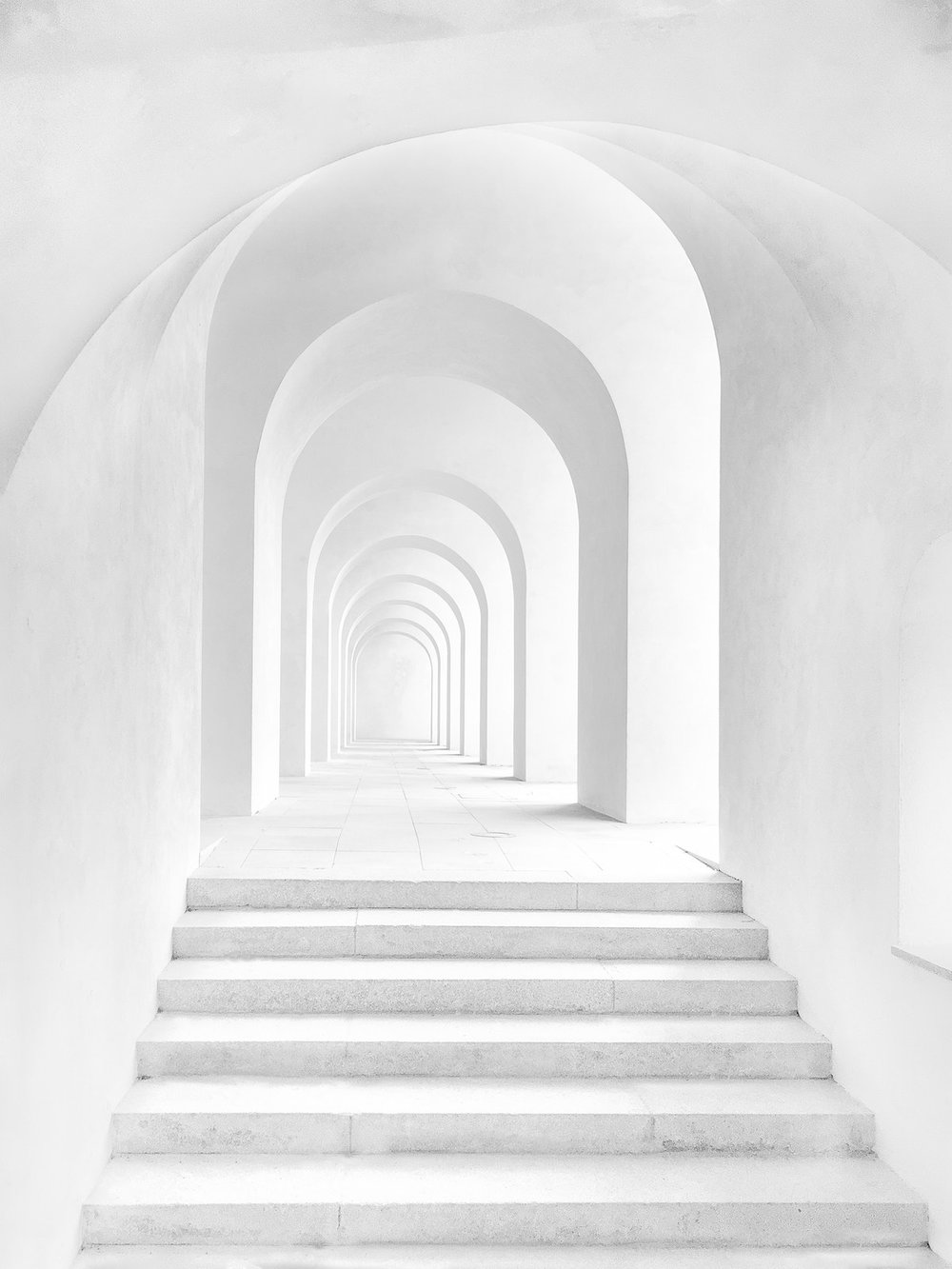 Arched hallway that is bright white, with steps leading up to the first archway