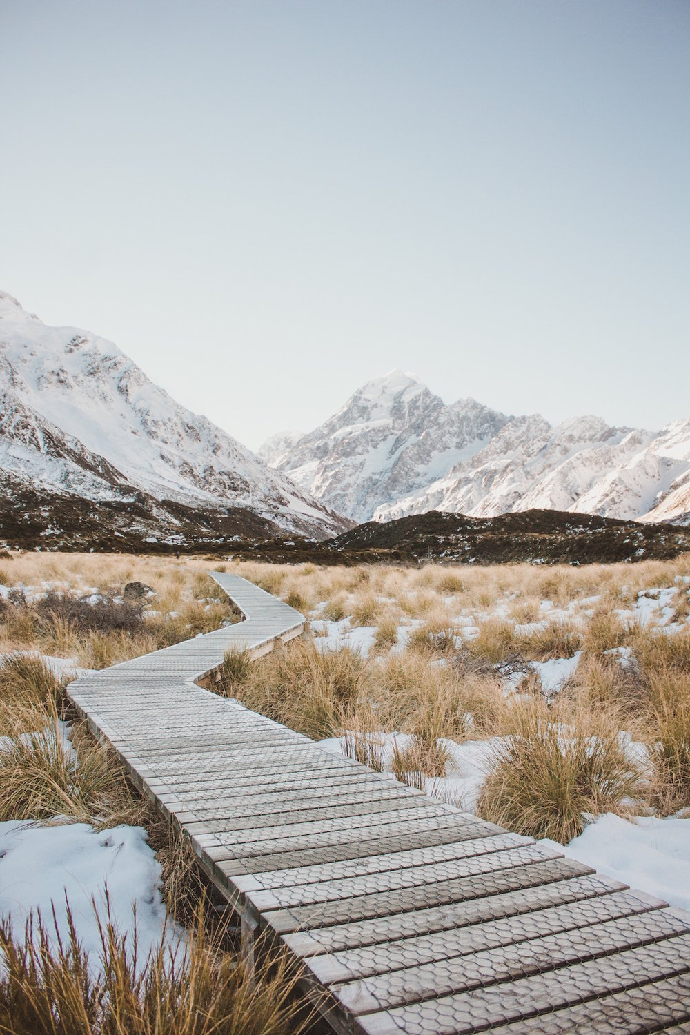 Wooden walking path over snowy fields, heading toward mountains