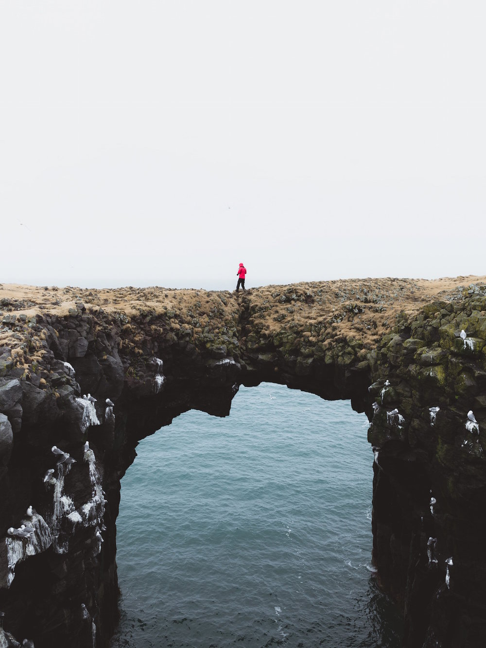 Natural archway over water made by rocky cliffs, with a person in a red jacket walking across