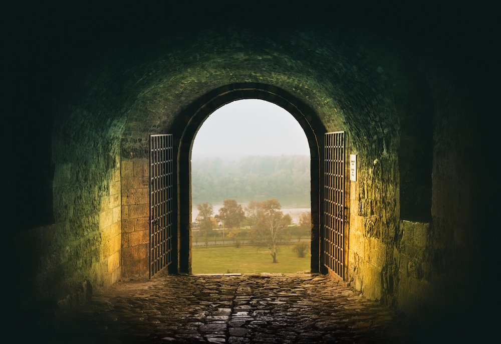 Stone tunnel leading to an open archway and a field of trees, warm and green light