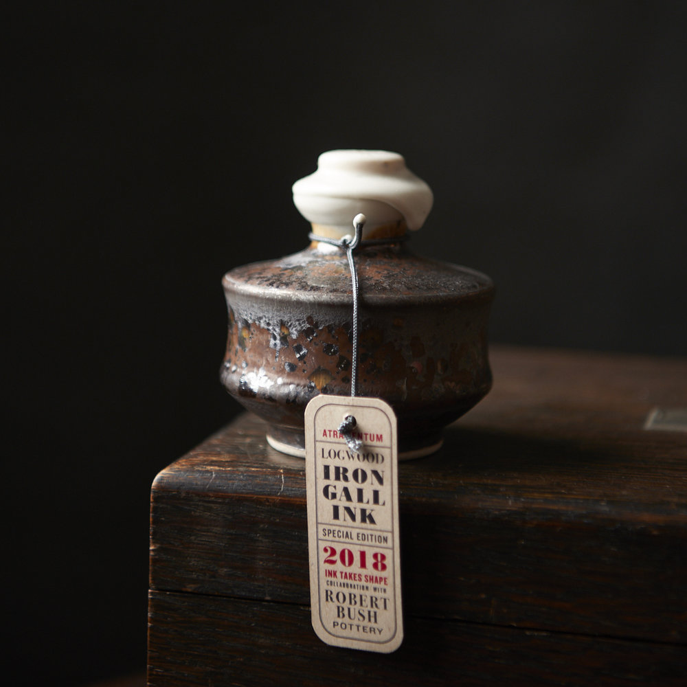 """LAUNCH DATE: MAY 10th 2018 — Sold Out.  This is a special formulation of traditional iron gall ink. The inclusion of logwood gives and ink with an immediate purple-black. The ink will oxidize to give a permanent, waterproof, black - as dark and profound as a starless night. Iron gall inks give clear hairlines and bold blacks when used for pointed pen or Spencerian calligraphy. The inclusion of logwood permits a significant reduction in the amount of ferrous contained in this ink.  This is a special vintage edition ink formulated by inkmaker Tim McLaughlin. The edition is part of the 2018 INK TAKES SHAPE project — a collaboration with British Columbia potter Robert Bush. Each pot of ink is in a hand thrown, porcelain vessel, commissioned especially for this ink. Each pot holds approximately 100ml (3.5 oz.) of ink. The pots are stoppered with a cork and sealed with wax. Each pot is numbered - there are only 40 pots in this edition.  The collaboration is part of the 2018 """"Ink Takes Shape"""" project. For dip pen or brush. Iron gall inks are not suitable for use in fountain pens. Shake gently before use."""