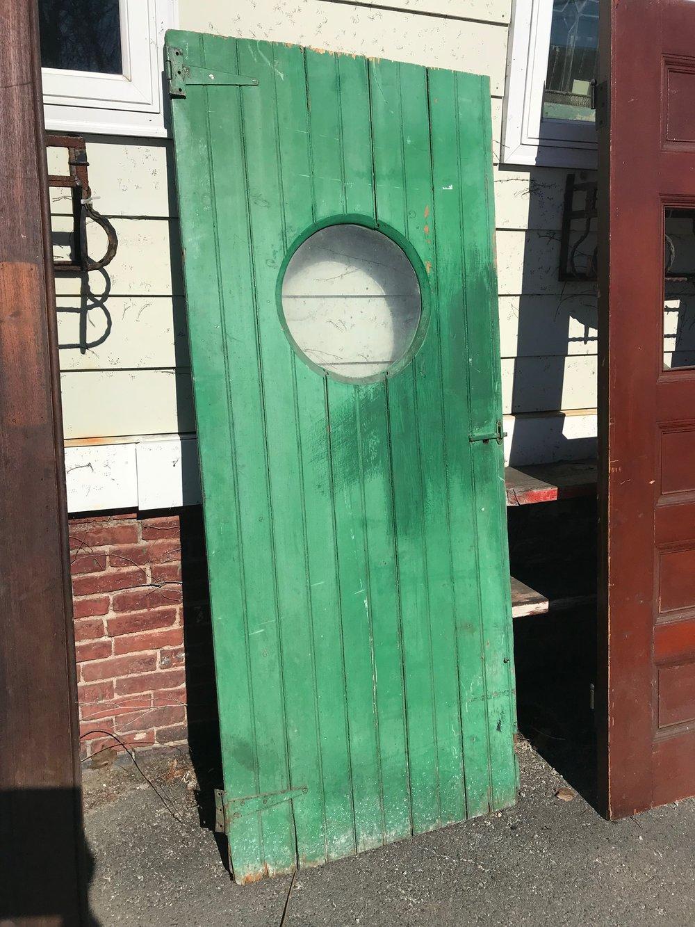 Antique bead board door with round window.