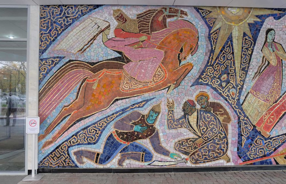 "A retelling of ""Enlik-Kebek"", 1965 , outside of the Hotel Almaty in Kazakhstana. A Kazakh folk tale about star-crossed lovers from different tribes, with a similar plot line to Romeo and Juliet. The mosaic storybook begins with the two lovers meeting on horseback and ends with their happy union after enduring trials and tribulations on the way. The first Soviet mosaics appeared in the 1930s, adorning the Stalinist neo-classical train stations, theaters and the Moscow metro. It then fell out of fashion in the 1950s under Nikita Khrushchev, but the monumentalist art aesthetic reappeared under Leonid Brezhnev in the late 1960s and 1970s. In the late Soviet period, any new public building automatically had 5% of the budget earmarked for ""artistic elements."" Many murals were created in the ""Stans"": Kazakhstan, Kyrgyzstan, Tajikistan, Turkmenistan and Uzbekistan. Though mosaics can last well with some help, they are left to disintegrate because people associate them with a fallen political system. Many of these murals are genuine art and were created by talented, experienced artists.  More about the forgotten Soviet mosaics in Central Asian Cities:  https://www.theguardian.com/cities/2017/oct/20/missing-murals-disappearing-soviet-art-stans"