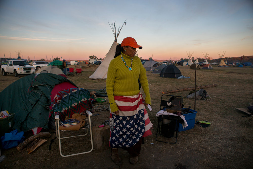 "Stacey Alkire, of Standing Rock Sioux Tribe, currently living in Denver, has been at the Seven Councils Camp for five weeks. Alkire said she was compelled to support her relatives at the camp ""because I'm tired of the govermenting screwing the Natives. They don't create balance with us."" She continues, ""All we want them to do is honor our treaties. I know this is a poverty-stricken place. But this is a beautiful place. We've never been honored. We've never been respected."" Saturday marked the 60th day of protest encampments surrounding the Dakota Access Pipeline near Cannon Ball, North Dakota. Law enforcement has reached out to federal agencies for both monetary and personnel assistance. Tensions have flared in recent weeks between law enforcement and protestors, as well as between private security and protestors. 