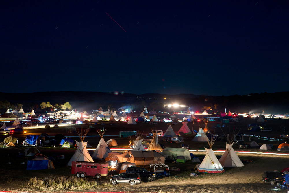 A long exposure shows the movement of activity at the Seven Councils Camp just after dusk on Saturday evening, Oct. 8, 2016. Saturday marked the 60th day of protest encampments surrounding the Dakota Access Pipeline near Cannon Ball, North Dakota. Law enforcement has reached out to federal agencies for both monetary and personnel assistance. Tensions have flared in recent weeks between law enforcement and protestors, as well as between private security and protestors. 