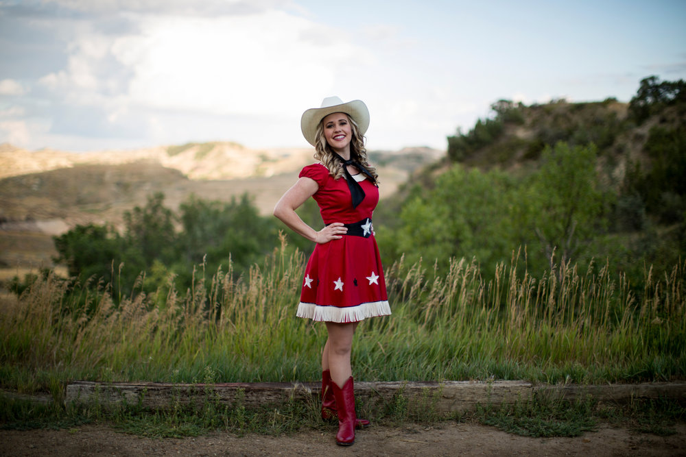 Burning Hills Singer Candice Lively Wollan behind the theatre before the evening's Medora Musical performance. Set against the natural backdrop of the rural North Dakota badlands, the Medora Musical offers audience members a unique outdoor theatre experience. The amphitheatre was built in 1958 and has been host to the Medora Musical since 1965. (Kristina Barker for the The New York Times)