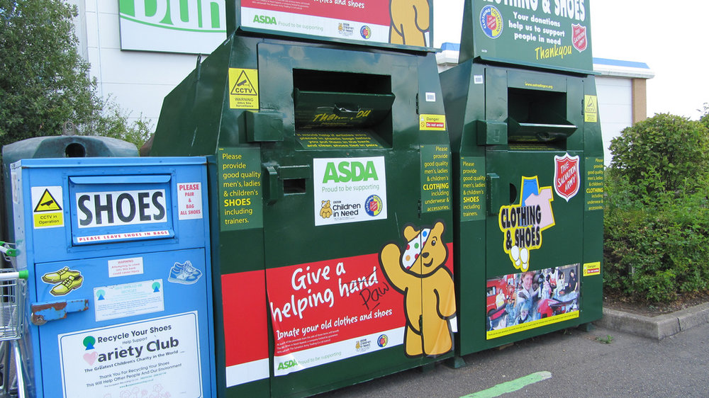 Bins for clothing donation in the United Kingdom. Even if sales benefit charities, most collected clothing will be sold overseas. Image by  Howard Lake via Flickr .