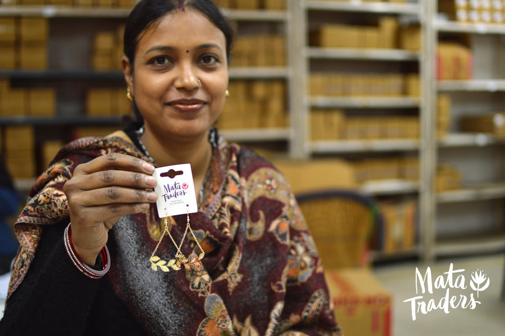 A Mata artisan holds up a brand label. Image courtesy of Mata Traders