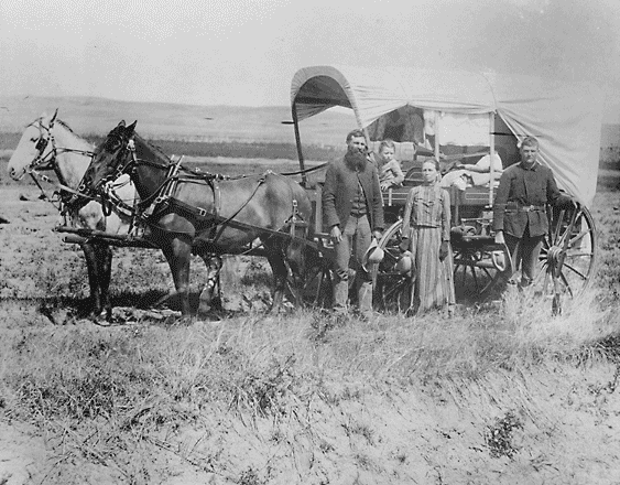 A family with their covered wagon during the Great Western Migration, 1866. Photo via National Archives.