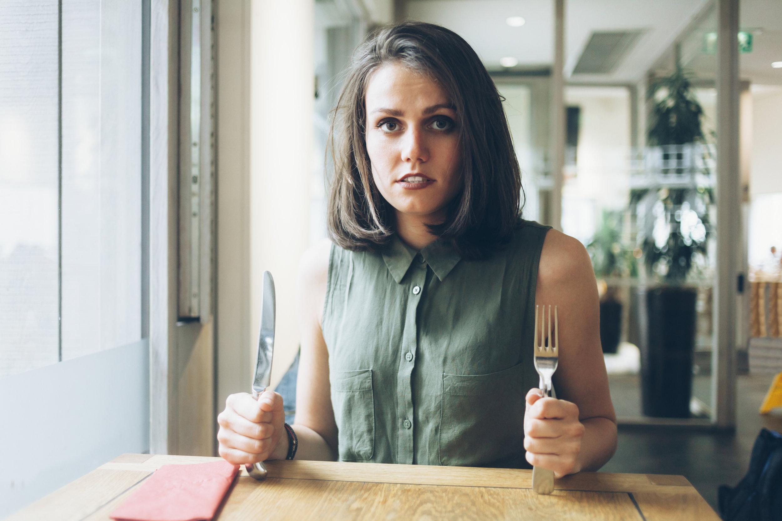 голодная женщина за столом с ножом и вилкой