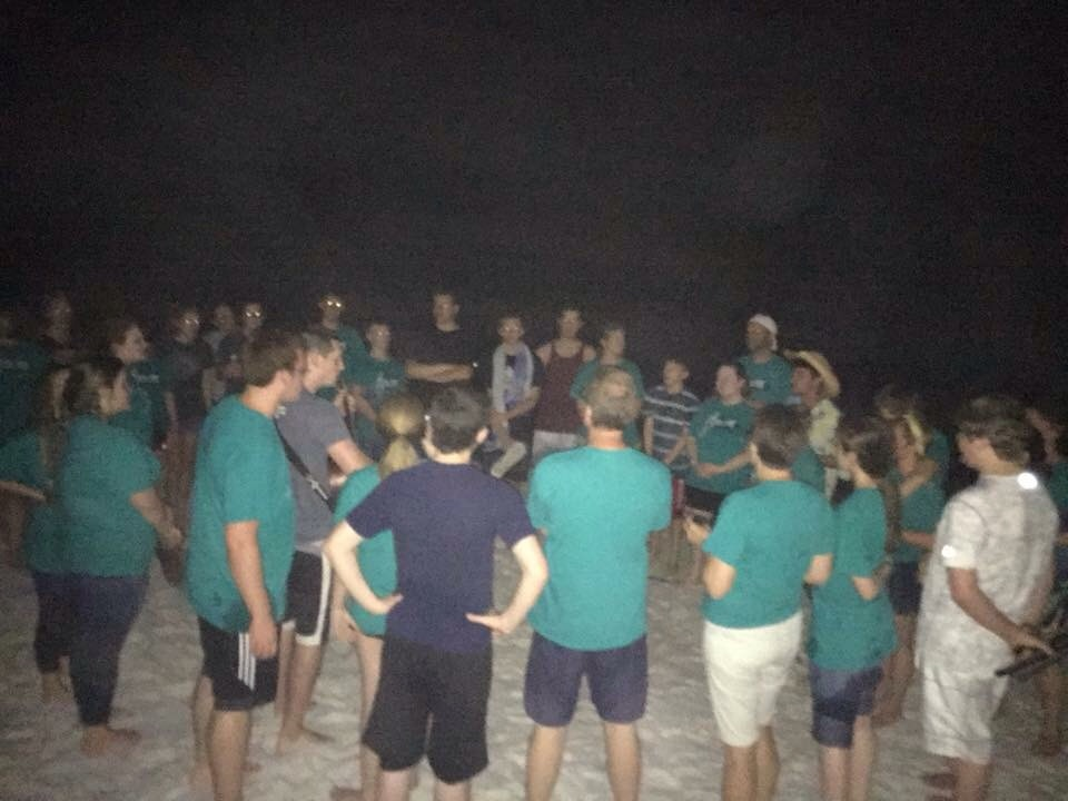Singing together on the beach at night.