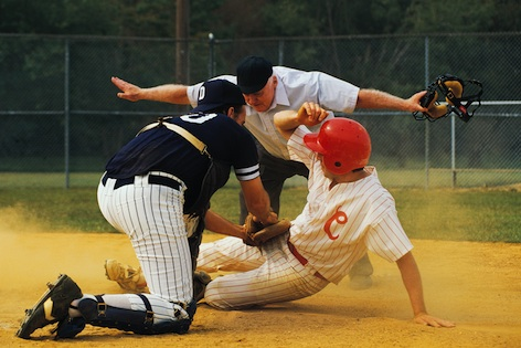 A player is tagged at a base. The referee indicates OUT! ©iStock
