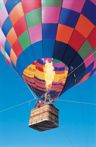 Heat makes the air inside the balloon less dense than the air outside, so the balloon floats. Getty Images